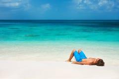 Jeune homme détendant sur la plage images stock