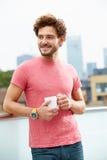 Jeune homme détendant sur la terrasse de toit avec la tasse de café Photographie stock