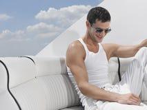 Jeune homme détendant sur Sofa Of Yacht Image libre de droits