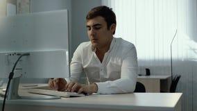 Jeune homme d'affaires à l'aide de l'ordinateur de bureau et notant l'information en bloc-notes banque de vidéos
