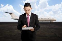 Jeune homme d'affaires à l'aide de son comprimé sur l'aéroport Images stock