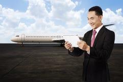 Jeune homme d'affaires à l'aide de son comprimé sur l'aéroport Images libres de droits