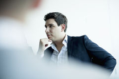 Jeune homme d'affaires écoutant lors d'une réunion d'affaires image stock