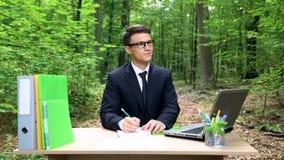Jeune homme d'affaires écrivant de bonnes idées, fonctionnant au bureau dans la forêt verte images libres de droits