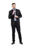 Jeune homme d'affaires élégant dans le costume attachant et ajustant la cravate Photo stock
