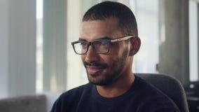 Jeune homme d'affaires africain de sourire sur le lieu de travail banque de vidéos
