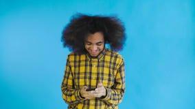 Jeune homme d'affaires africain heureux à l'aide du téléphone et obtenant de bonnes nouvelles sur le fond bleu Concept des ?motio banque de vidéos