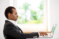 Jeune homme d'affaires africain réussi dactylographiant sur l'ordinateur portable, se reposant sur le lieu de travail Photos libres de droits