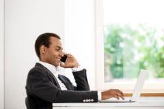 Jeune homme d'affaires africain réussi parlant du téléphone, ordinateur portable de dactylographie Photographie stock libre de droits