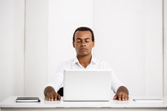 Jeune homme d'affaires africain réussi s'asseyant sur le lieu de travail avec l'ordinateur portable Photo stock