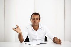 Jeune homme d'affaires africain réussi s'asseyant sur le lieu de travail avec le carnet Photographie stock