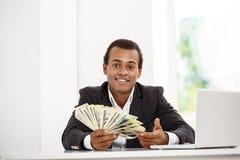 Jeune homme d'affaires africain réussi souriant, tenant l'argent, se reposant sur le lieu de travail Photographie stock libre de droits