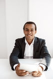 Jeune homme d'affaires africain réussi souriant, tenant le comprimé, se reposant sur le lieu de travail Image stock