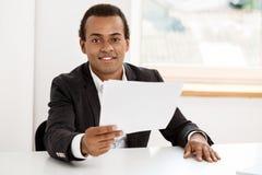 Jeune homme d'affaires africain réussi souriant, tenant le papier, se reposant sur le lieu de travail Photo libre de droits
