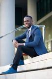 Jeune homme d'affaires amical s'asseyant sur des étapes dans la ville Image libre de droits