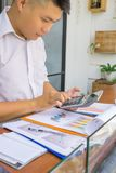 Jeune homme d'affaires asiatique à l'aide de la calculatrice image libre de droits