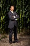 Jeune homme d'affaires asiatique devant une zone de maïs Photos stock