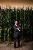 Jeune homme d'affaires asiatique devant une zone de maïs Images stock