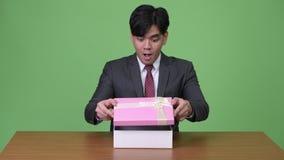 Jeune homme d'affaires asiatique semblant heureux et étonné tout en ouvrant le boîte-cadeau banque de vidéos