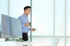 Jeune homme d'affaires asiatique tenant le smilin de tasse et de smartphone de café photographie stock libre de droits