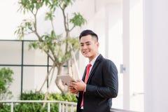 Jeune homme d'affaires asiatique travaillant au comprimé, mode de vie de mâle moderne technologie pour communiquer, de message ou image libre de droits