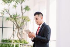 Jeune homme d'affaires asiatique travaillant au comprim?, mode de vie de m?le moderne technologie pour communiquer, de message ou photos libres de droits