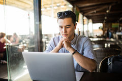 Jeune homme d'affaires asiatique travaillant avec l'ordinateur portable et le carnet dans l'entrepreneur occasionnel de café Trav image stock