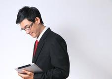 Jeune homme d'affaires asiatique utilisant un réseau de PC de comprimé image libre de droits