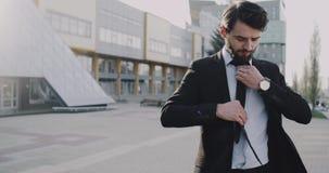 Jeune homme d'affaires attendant une réunion devant le bâtiment d'affaires clips vidéos
