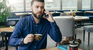 Jeune homme d'affaires attirant barbu s'asseyant à la table en bois dans le restaurant, parlant sur le téléphone et le thé potabl Image stock