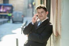Jeune homme d'affaires attirant et occupé avec des yeux bleus portant des affaires parlantes de costume et de lien au téléphone p photos stock