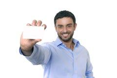 Jeune homme d'affaires attirant heureux tenant la carte de visite professionnelle vierge de visite avec l'espace de copie Photographie stock