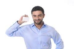 Jeune homme d'affaires attirant heureux tenant la carte de visite professionnelle vierge de visite avec l'espace de copie Image libre de droits