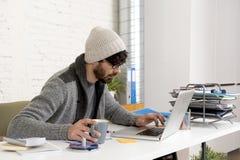 Jeune homme d'affaires attirant hispanique de hippie de portrait d'entreprise travaillant avec le siège social moderne d'ordinate Photo libre de droits