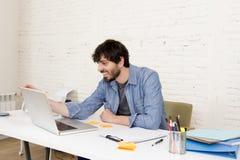 Jeune homme d'affaires attirant hispanique de hippie de portrait d'entreprise travaillant avec le siège social moderne d'ordinate Photos stock