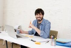 Jeune homme d'affaires attirant hispanique de hippie de portrait d'entreprise travaillant avec le siège social moderne d'ordinate Image stock