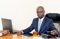 Jeune homme d'affaires au bureau avec l'ordinateur portable et le téléphone Photographie stock libre de droits