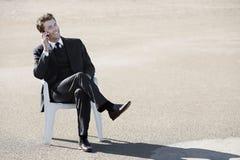 Jeune homme d'affaires au téléphone dans le désert Photographie stock libre de droits