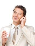 Jeune homme d'affaires au téléphone tout en buvant d'un café Photos stock