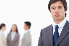 Jeune homme d'affaires avec l'équipe derrière lui Photo libre de droits