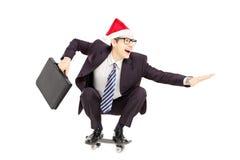 Jeune homme d'affaires avec la serviette et le chapeau de Santa montant un skateboa Photos stock