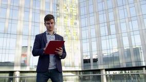 Jeune homme d'affaires avec le dossier de reliure à anneaux sur la rue de ville banque de vidéos