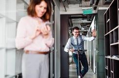 Jeune homme d'affaires avec le scooter dans un immeuble de bureaux, faisant une pause photo stock