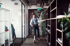 Jeune homme d'affaires avec le scooter dans un immeuble de bureaux, faisant une pause image libre de droits
