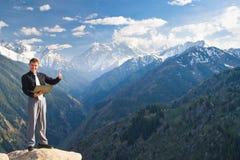 Jeune homme d'affaires avec un large sourire sur le dessus de montagne Image libre de droits