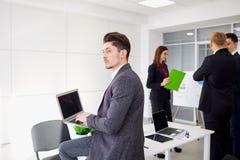Jeune homme d'affaires avec un ordinateur portable dans les mains des travaux dans le backgr Photos libres de droits