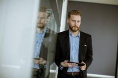 Jeune homme d'affaires avec un PC de comprimé au bureau photos stock