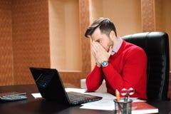 Jeune homme d'affaires avec un problème au bureau se reposant à son bureau fronçant les sourcils à son écran d'ordinateur photographie stock libre de droits