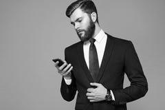 Jeune homme d'affaires avec une barbe tenant un téléphone photographie stock libre de droits