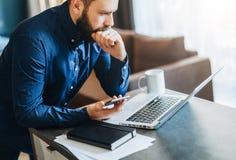 Jeune homme d'affaires barbu sérieux travaillant sur l'ordinateur, tenant le smartphone, pensant L'homme analyse l'information, p image libre de droits